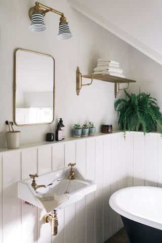 Wood panelled bathroom with black bath