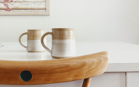 Two two-tone cream mugs on a white table