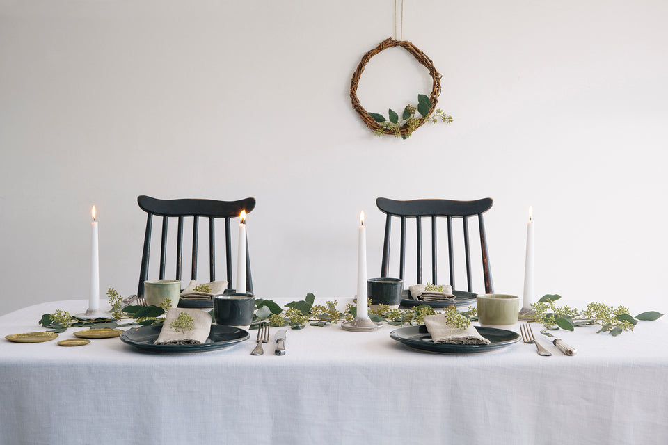 Table laid with handmade plates and linen table cloth