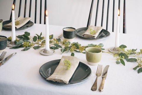 A table laid with grey plates and cream napkins with green foliage