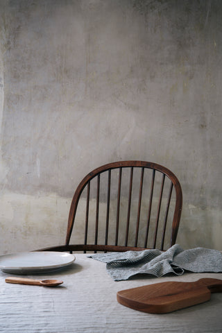 a rounded back spindle chair behind a table covered with linen