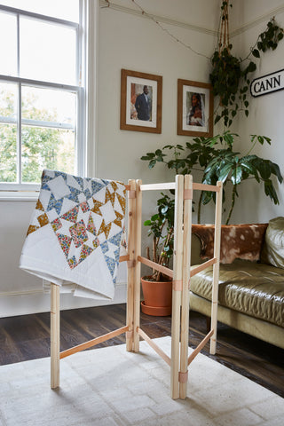 A wooden drying rack with a quilt hung over it
