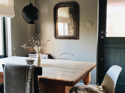 a wooden dining table in front of a dark door and antique mirror