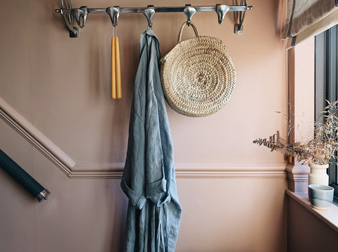 a pink wall with hooks on which a bag, denim dress and amber candles hang
