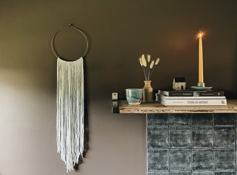 Brown walls with macrame and mantlepiece with trinkets