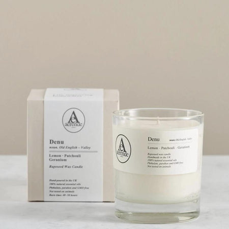 A clear glass jar candle in front of a pale grey candle box