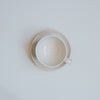 Cream stoneware coffee cup and saucer from above
