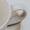 Close up of cream coffee cup and saucer handle