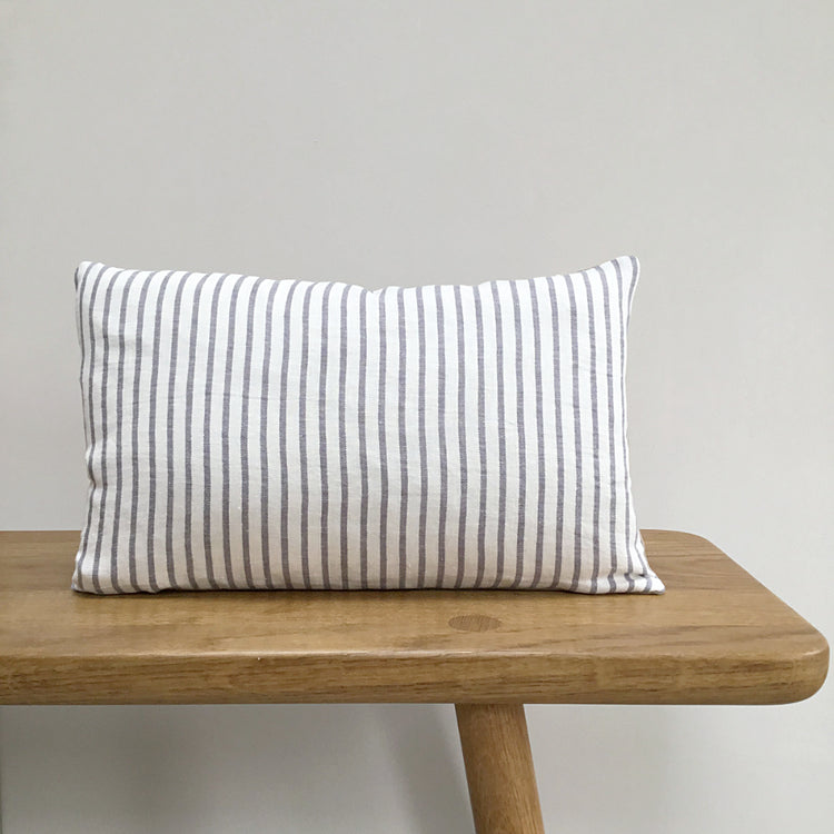 Grey and white Stripe Linen Lumbar Cushion On A Wooden Bench