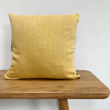 mustard yellow cushion on a bench