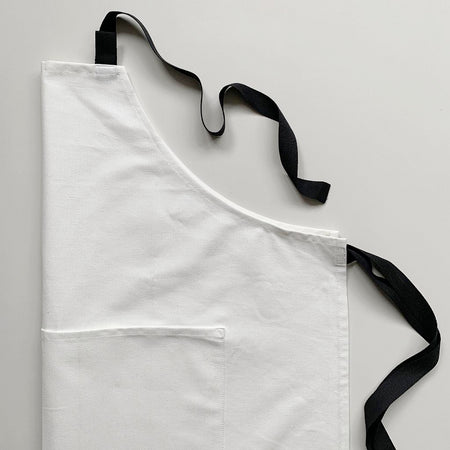 Off white cotton apron with black straps