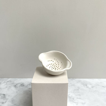 A perforated handmade white tea strainer on a cream box