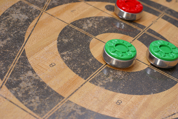 Shuffleboard Pucks Resting On A Poorly Maintained Shuffleboard Table