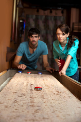 Two people testing shuffleboard pucks and trying to choose the best shuffleboard table.