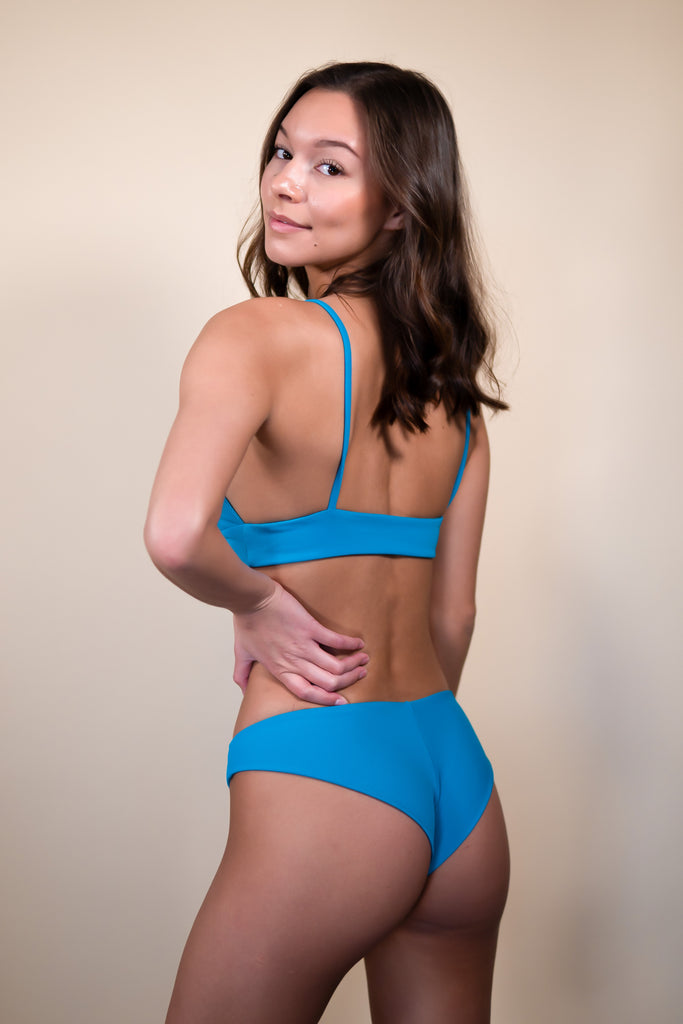 turquoise cheeky style bottom with a detailed seam down the back of the suit.