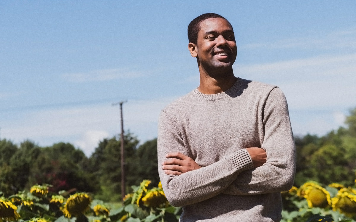 Younger man standing, smiling in a field of sunflowers.