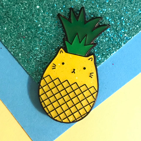 A yellow enamel pin combining the shape of a cat and a pineapple
