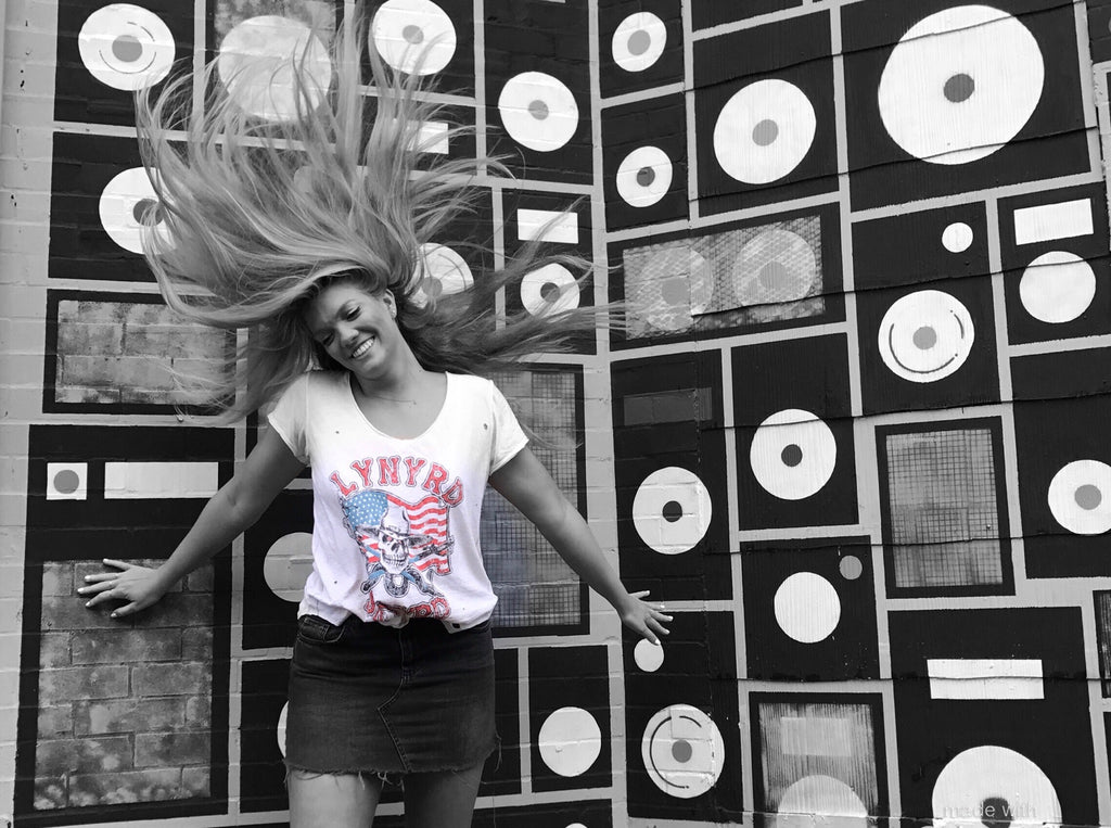 cute blonde girl in front of the Grimey's mural, tossing her long hair, wearing a Lynrd Skynrd retro concert T-shirt by Trunk Ltd
