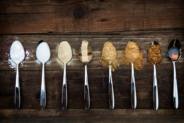 A range of different sugar types on spoons