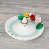 Glass flowers adorn white ceramic ring holder with splash of aqua blue