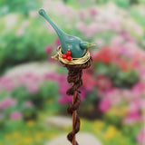 Turquoise bird accented with red berries tops a unique garden plant stake gift
