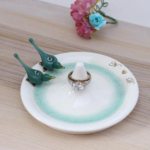 White ceramic ring holder decorated with pair of glass turquoise bird
