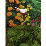 Whimsical bird plant stake charms in flower garden
