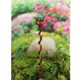 Decorative garden art plant stake with green bird in copper nest