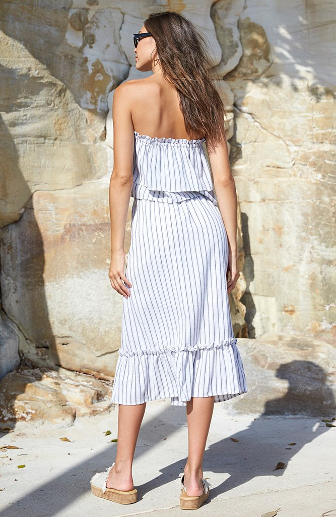 Model is wearing white double frill Minkpink top. The Baja layered strapless top has thin navy stripes running vertically throughout.