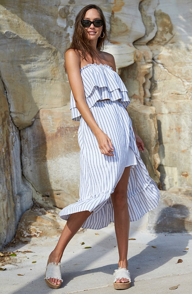 Model is wearing a white, midi, high-waisted skirt by Minkpink. The Baja Faux wrap midi skirt has a ruffle detailing along the hem and slit on the left leg. The white is contrasted with thin deep navy vertical lines.