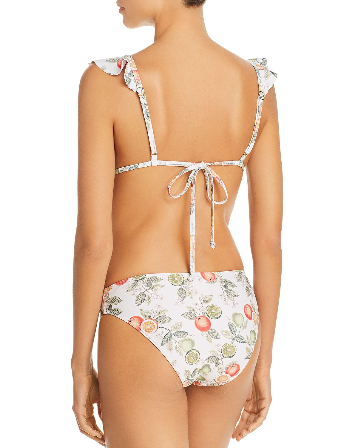 Model is wearing a multicoloured bikini top with spaghetti straps, the back features a simple tie closure. The fabric print has green and orange citrus fruits with greenery on a white background.