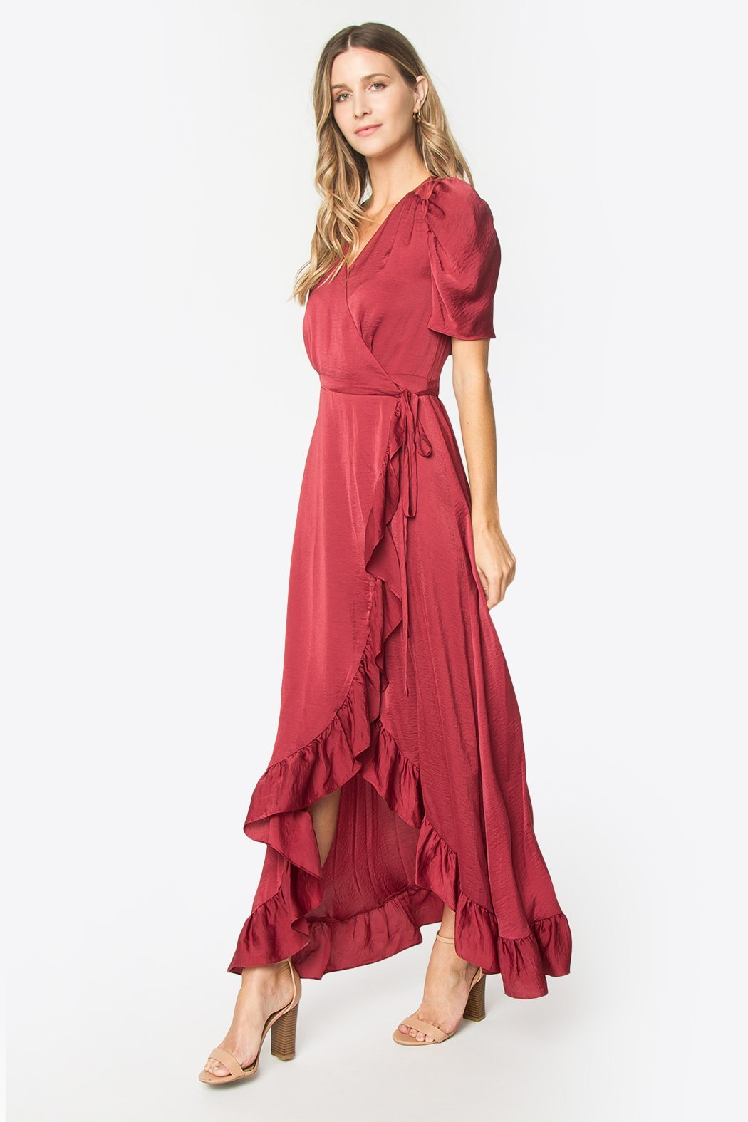 Front view of model wearing a dark coral, light-weight, silky dress which features t-shirt length puff sleeves, a wrap tie closure, v-neckline, and a decorative ruffle along the whole hi-low hem line.