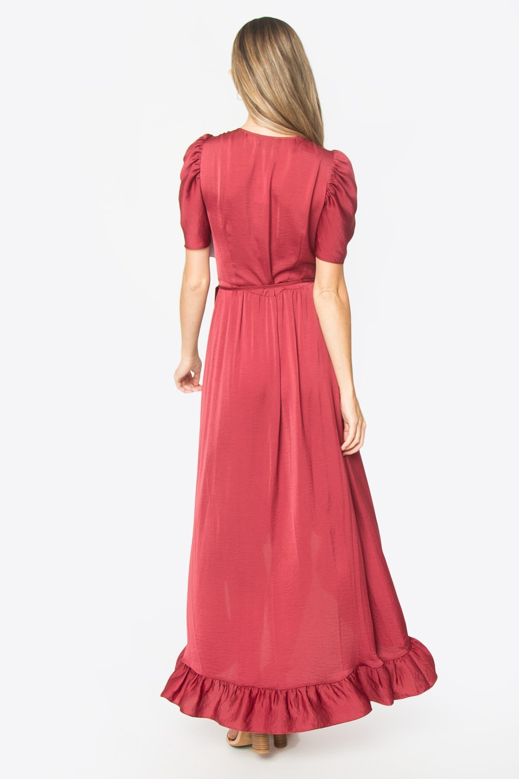 Back view of model wearing a dark coral, light-weight, silky dress which features t-shirt length puff sleeves, a wrap tie closure, v-neckline, and a decorative ruffle along the whole hi-low hem line.