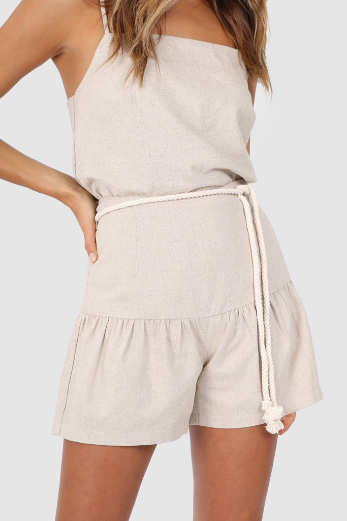 UNIKONCEPT Lifestyle boutique: the image shows the Georgia Short by Lost in Lunar. These high waisted, relaxed silhouette shorts come in a sand colour and feature a fluted leg. Around the waist is a white rope detail to accentuate your figure to the max. These shorts are a conservative length to keep you comfortable.