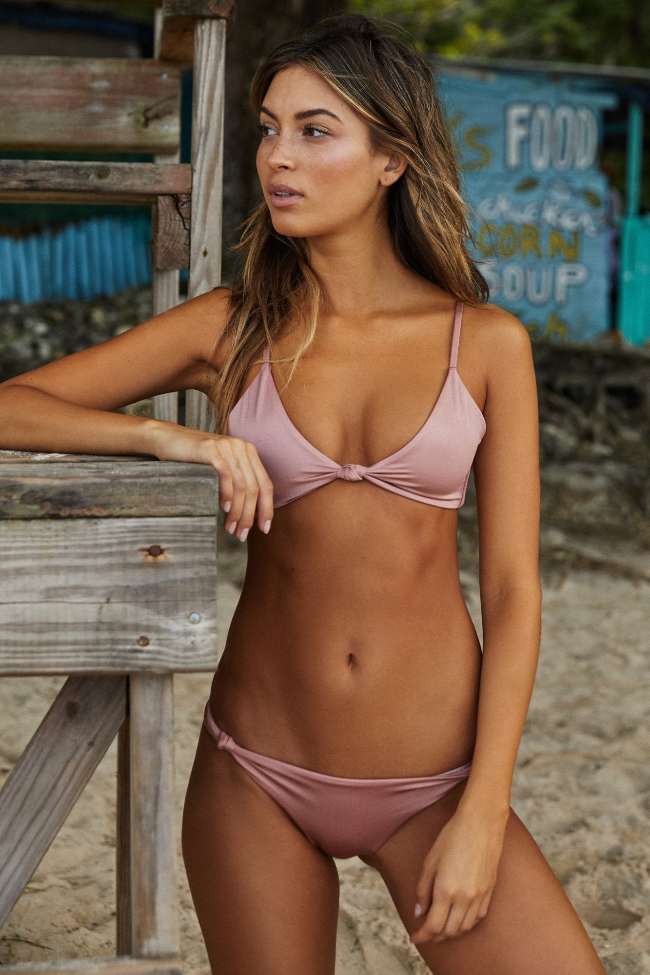 Front view of model wearing light, dusty pink low-rise bikini bottoms featuring knotted side detail.