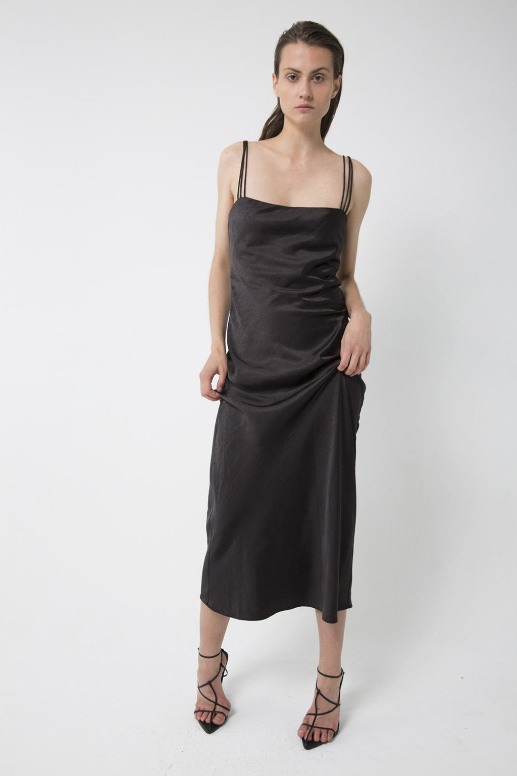 UNIKONCEPT lifestyle boutique: Model is wearing black, satin, midi third form slip dress. The 90's bias midi slip dress comes with 3 strap detail and square neckline.