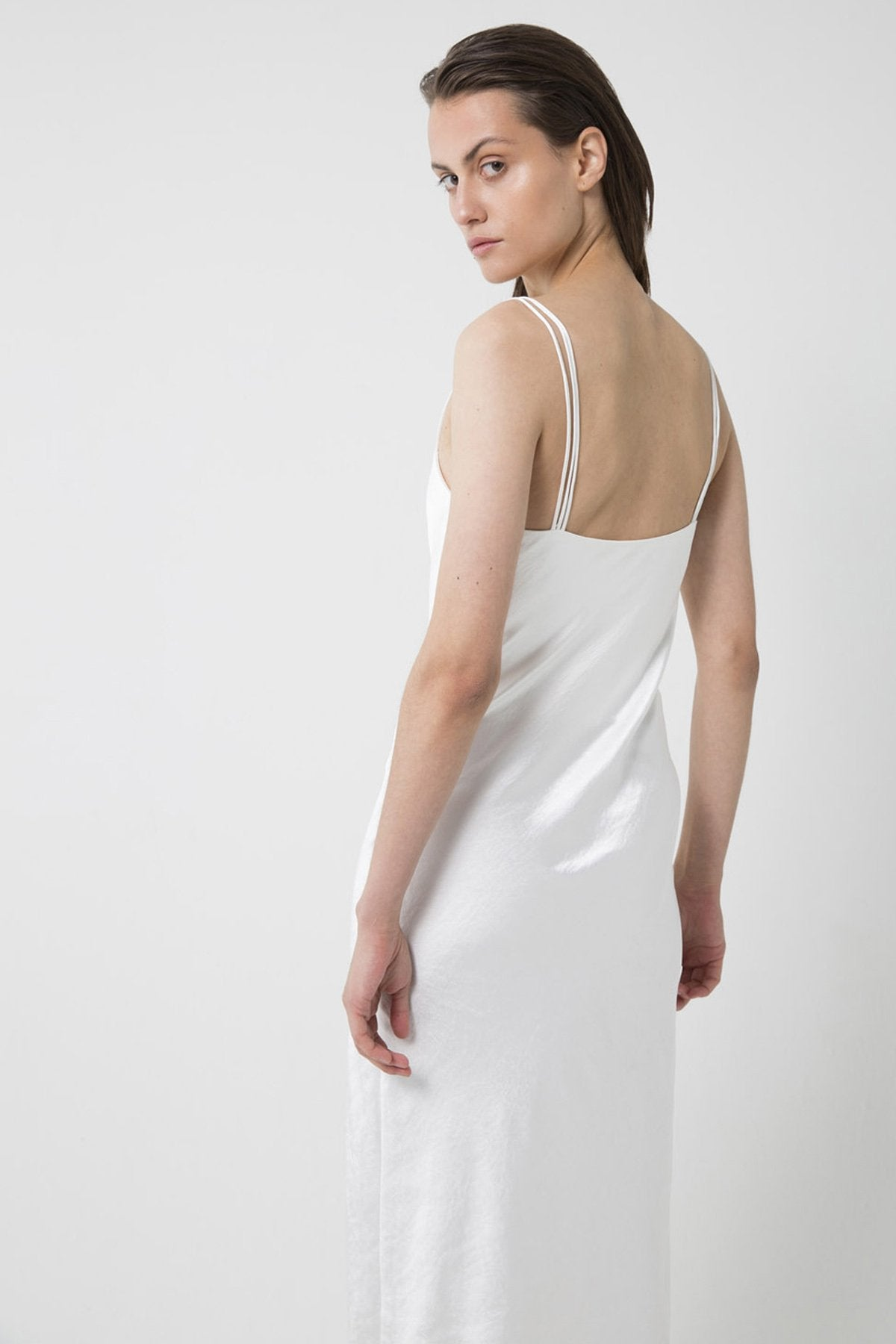 UNIKONCEPT lifestyle boutique: Bridal wear: Model is wearing white, satin, midi third form slip dress. The 90's bias midi slip dress comes with 3 strap detail and square neckline.
