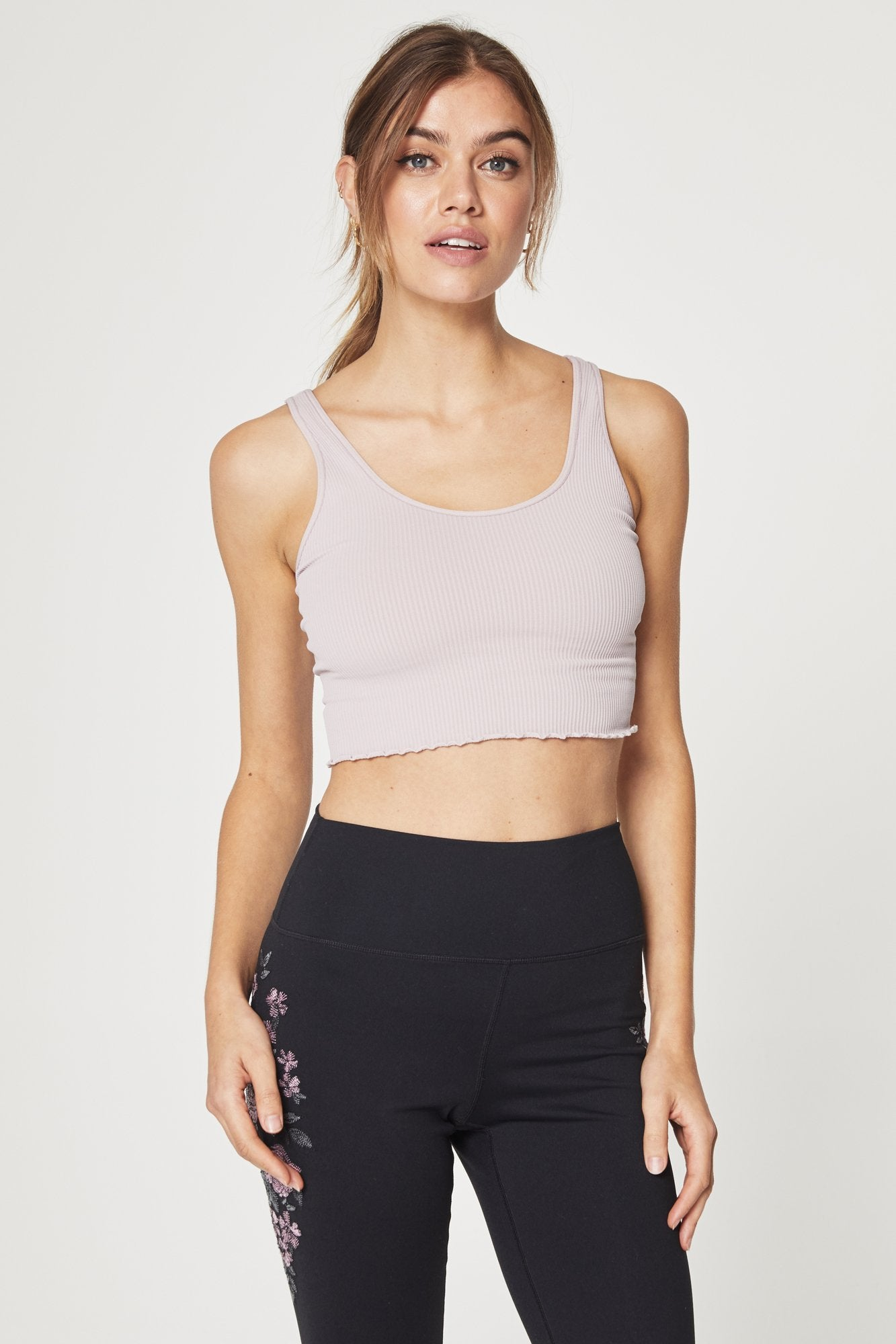 Front view of model wearing sleeveless, crop-length, rose-quartz, spiritual gangster tank top. The Amor crop active tank in rose quartz features half inch straps, a scoop neckline, ribbed fabric, and a ruffled hem.