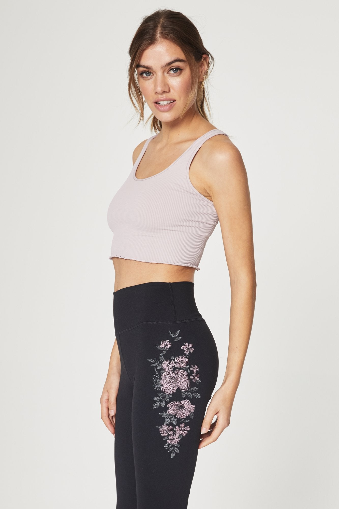 Side view of model wearing sleeveless, crop-length, rose-quartz, tank top. It features half inch straps, a scoop neckline, ribbed fabric, and a ruffled hem.