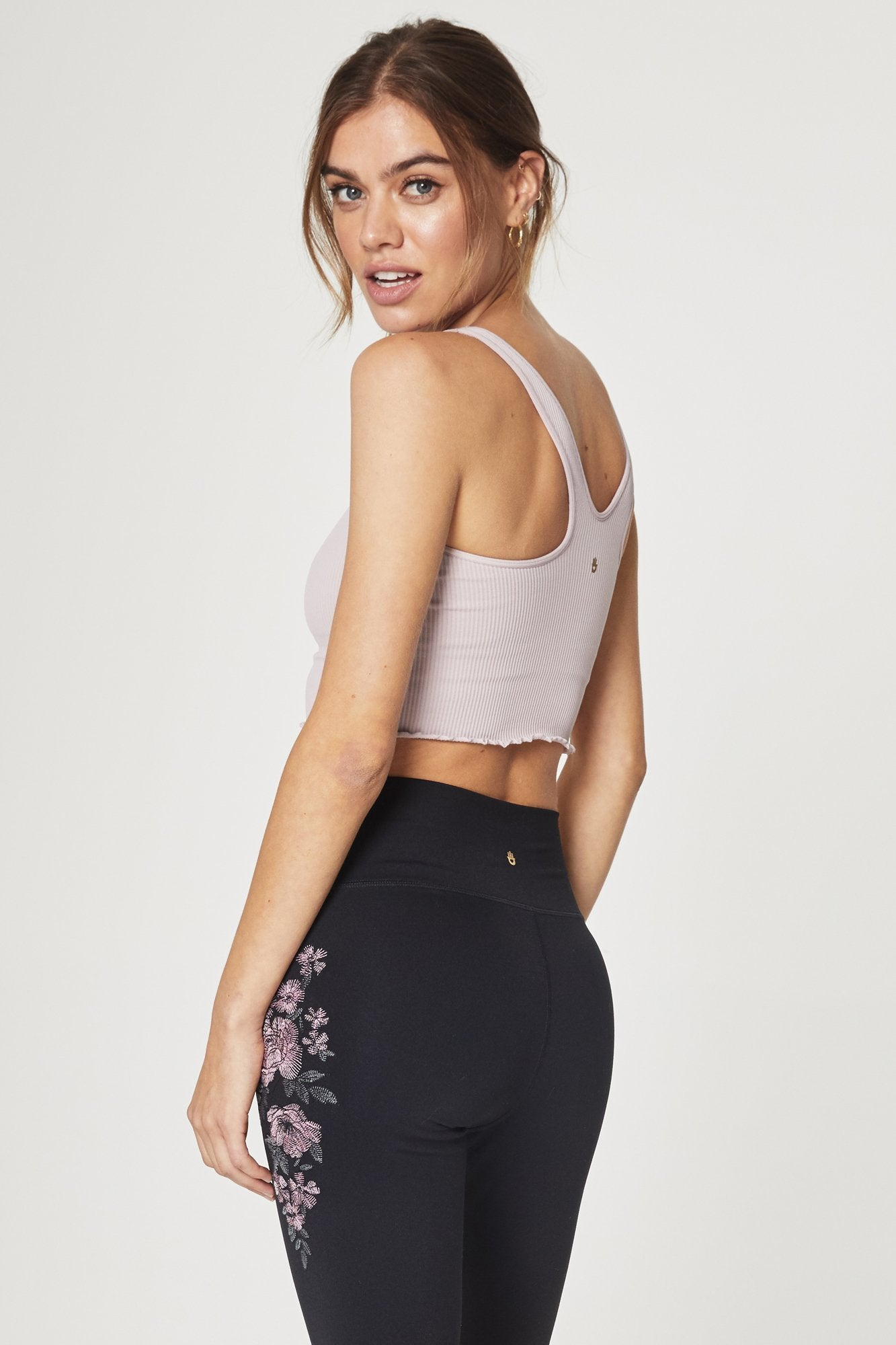 Front view of model wearing sleeveless, crop-length, rose-quartz, tank top. It features half inch straps, a v-back, ribbed fabric, and a ruffled hem.