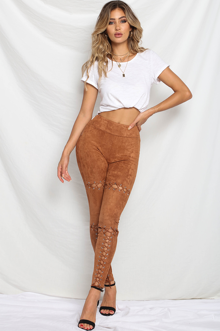 Model is wearing bronze, faux-suede, leggings with eyelet and lace-up detailing along the middle line of both legs.