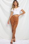 Model is wearing bronze, faux-suede, runaway leggings. The vixen pants in bronze comes with eyelet and lace-up detailing along the middle line of both legs.