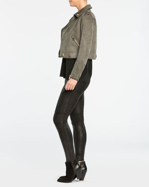 Model wearing black moto, slimming leggings in faux leather fabric. Moto details include ribbing along legs. View from side.