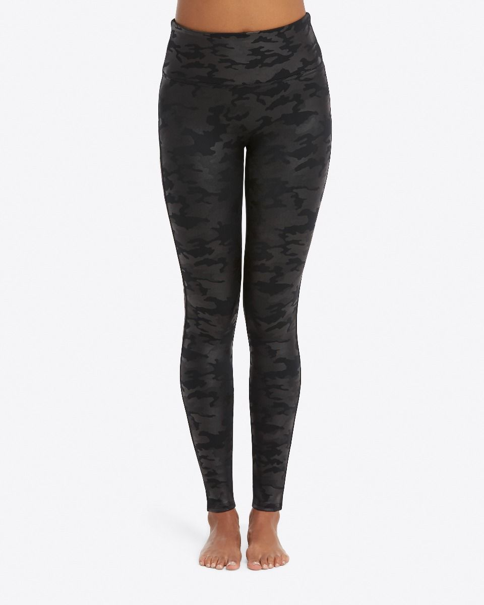 Model wearing black camo, slimming leggings in faux leather fabric. Camo detailing throughout leggings.