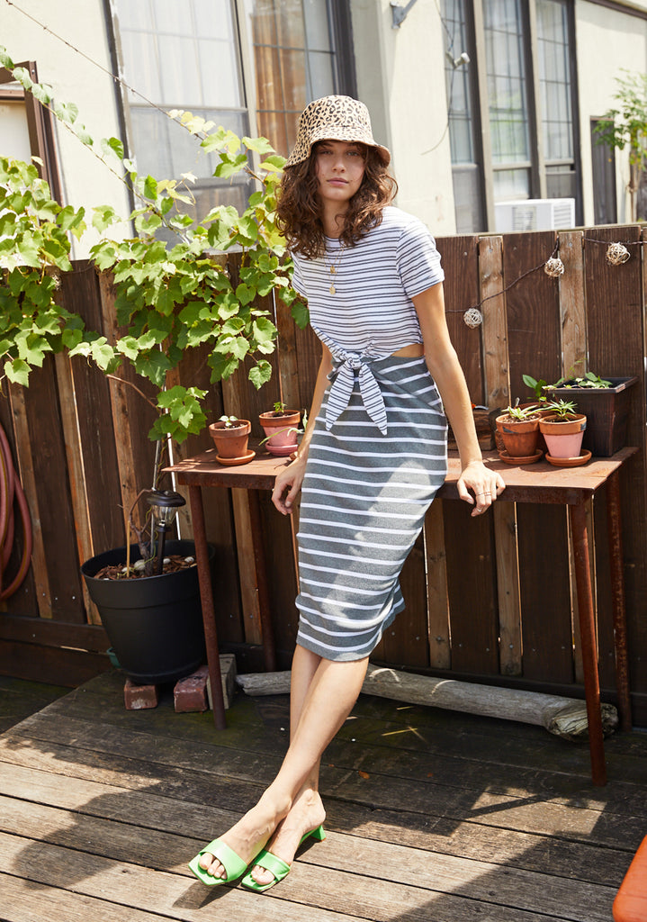 UNIKONCEPT: Lifestyle boutique; image shows a tee shirt styled midi dress with horizontal stripes. The Naomi dress is two toned with the top portion (waist to collarbone) white base with black horizontal stripes and the bottom Half as a black base with white horizontal stripes. This dress also features a cut out mid section with a tie in order to accentuate the waist.