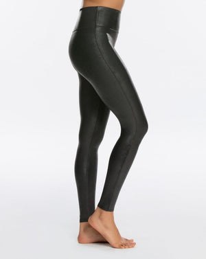 Model wearing black, slimming leggings in faux leather fabric. View from side.