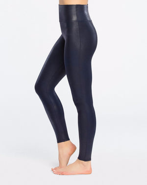 Model wearing navy (blue), slimming leggings in faux leather fabric. View from side.