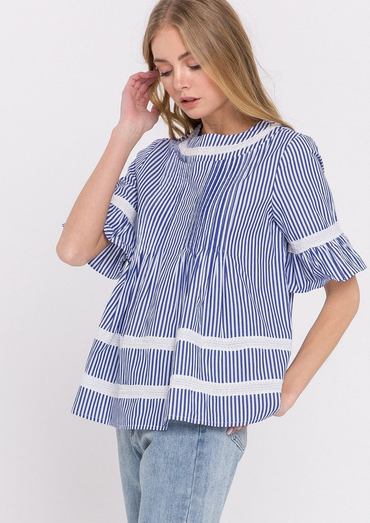 UNIKONCEPT Lifestyle boutique: image shows the Blue Lace Poplin Blouse by English Factory. This top is a looser styled, full length t-shirt blouse with a rounded neckline, and blue and white vertical stripes. The fabric is minimally cinched along the waist then flows freely. There is a lace detailed white strip along the neck line, the sleeves, and two horizontal strips along the bottom of the shirt. The shirt is closed at the back by 6 buttons that go down the whole length of the blouse.