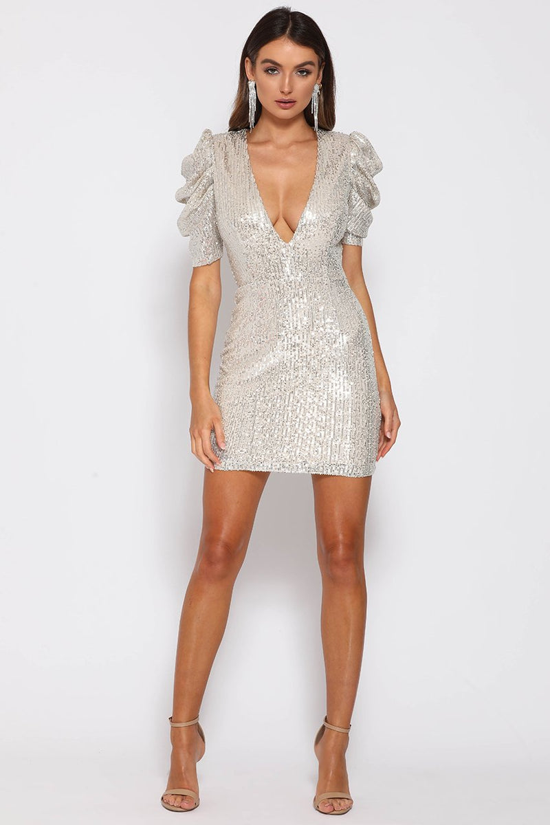 UNIKONCEPT: Lifestyle boutique; Image shows a fully sequinned mini dress. The disco pouffe mini dress features elbow length sleeves, an extreme plunge neckline and a rouched, puffy like sleeve. Pre completely covered the dress shoulders to mid thigh in a gorgeous silver sequin and has a white gold base.