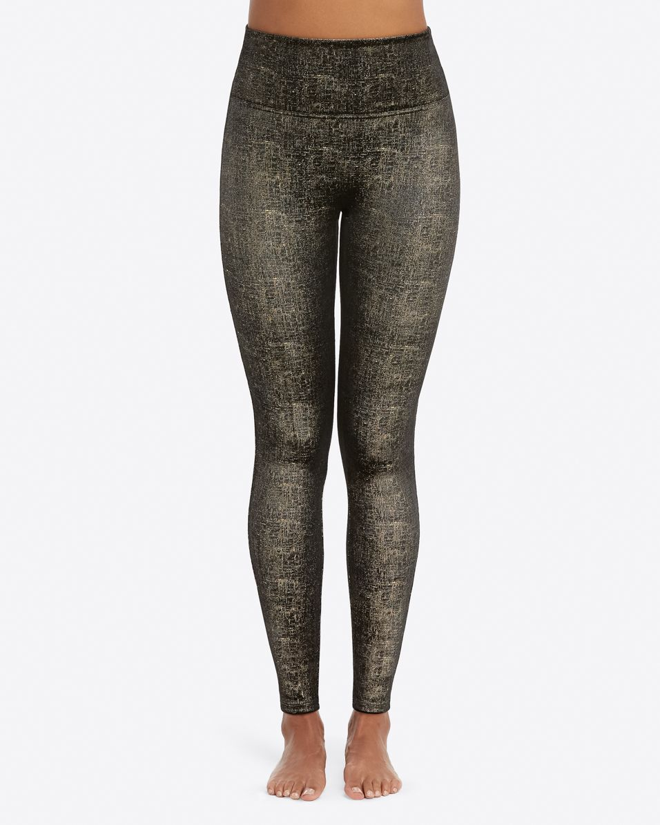 UNIKONCEPT Lifestyle boutique: Model wearing black, slimming Spanx leggings in velvet fabric. The velvet leggings in gold and black have Gold details throughout.